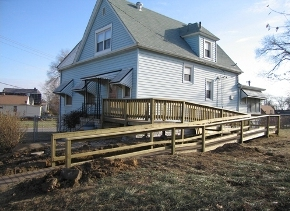 Horizontal boards between support posts provide a railing on this wheelchair ramp.